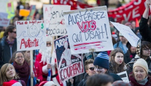 Protesters hold up signs during an anti-austerity demonstration in Montreal Friday, October 31, 2014. (Graham Hughes / THE CANADIAN PRESS)