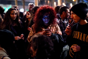 A girl dressed as a zombie checks her cell phone as she takes part in a 'Zombie Walk' in central Belgrade, Serbia, Sunday, Oct. 26, 2014. (AP / Marko Drobnjakovic)