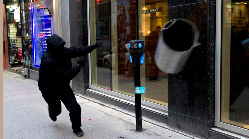 A demonstrator throws a trash can at a store during a march against police brutality Thursday, March 15, 2012 in Montreal. Protesters lobbed objects at officers, vandalized a few stores and smashed one police vehicle. Authorites responded by firing off chemical irritants in a bid to disperse a crowd of about 1,000 people.THE CANADIAN PRESS/Paul Chiasson