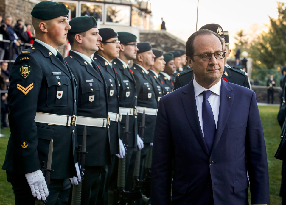 French President Francois Hollande, right, inspects an honour guard in Banff, Alta., on Sunday, Nov. 2, 2014. (Jeff McIntosh / THE CANADIAN PRESS)