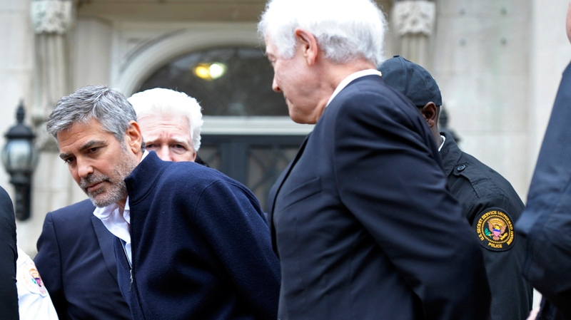 George Clooney, center, Rep. Jim Moran, D-Va, back, and Clooney's father, Nick Clooney, right, are arrested during a protest at the Sudanese Embassy in Washington, Friday, March 16, 2012. (AP / Cliff Owen)