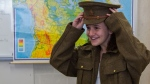 Student Simone Boivin tries on a replica Canadian military jacket from the First World War as part of the Supply Line program.