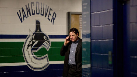 Vancouver Canucks' owner Francesco Aquilini speaks on his mobile phone as general manager Mike Gillis, not pictured, speaks to reporters down the hallway in Vancouver, B.C., on Monday April 25, 2011. (THE CANADIAN PRESS/Darryl Dyck)