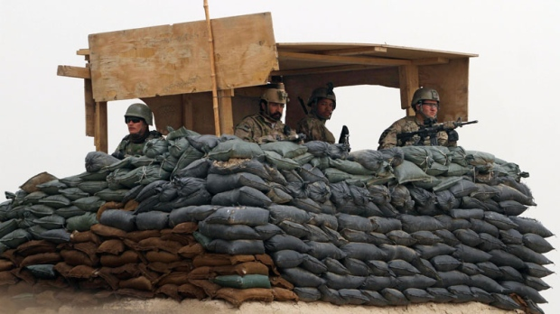 In this Sunday, March 11, 2012 file photo, U.S. Army and Afghan soldiers are seen in a guard tower at their base in Panjwai, Kandahar province south of Kabul, Afghanistan. (AP / Allauddin Khan)