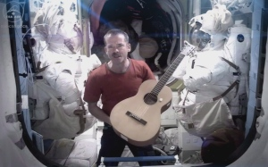 Canadian Astronaut and ISS commander Chris Hadfield is framed by spacesuits as he performs David Bowie's Space Oddity on the International Space Station, published on Sunday May 12, 2013. (THE CANADIAN PRESS/HO, CSA - Chris Hadfield)