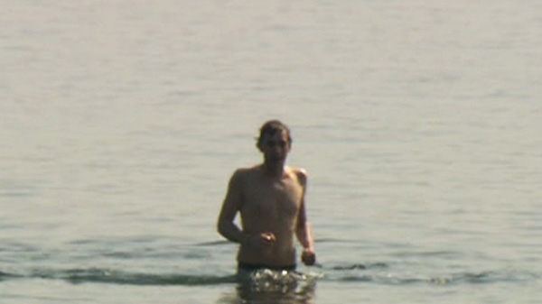 A man takes advantage of the warm weather in Toronto and goes for a swim at Cherry Beach on Friday, March 16, 2012.