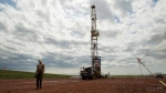 Austin Mitchell walks away from an oil derrick outside of Williston, N.D., Tuesday, July 26, 2011. (AP / Gregory Bull, File)