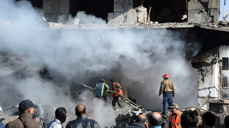 Syrian firefighters extinguish a fire in a damaged building near the aviation intelligence department, which was attacked by one of two explosions, in Damascus, Syria, on Saturday, March 17, 2012.