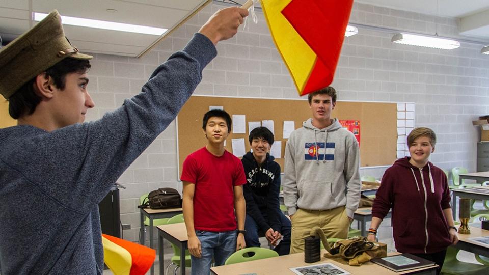 A student raises a flag