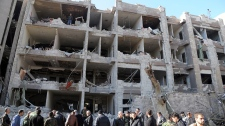 In this photo released by the Syrian official news agency SANA, Syrian security officers investigate a damaged building of the air intelligence forces, which was attacked by one of two explosions, in Damascus, Syria, on Saturday, March 17, 2012. (AP Photo/SANA)