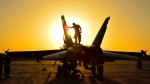 Royal Canadian Air Force ground crew performs post flight checks on a CF-18 fighter jet in Kuwait after a sortie over Iraq during Operation IMPACT on Nov. 3, 2014. (Canadian Forces Combat Camera / Department of National Defence)