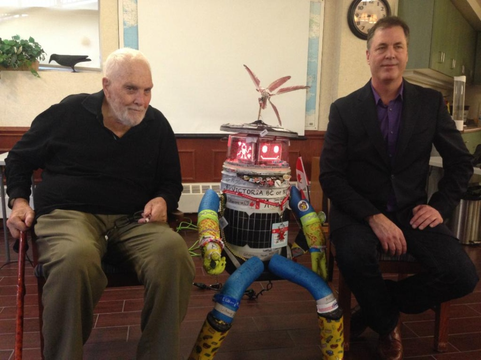 Hitchbot sits between its 'father', David Smith (right), and 'grandfather' Rod Smith (left) in Waterloo, Ont., on Tuesday, Nov. 4, 2014. (Dan Lauckner / CTV Kitchener)