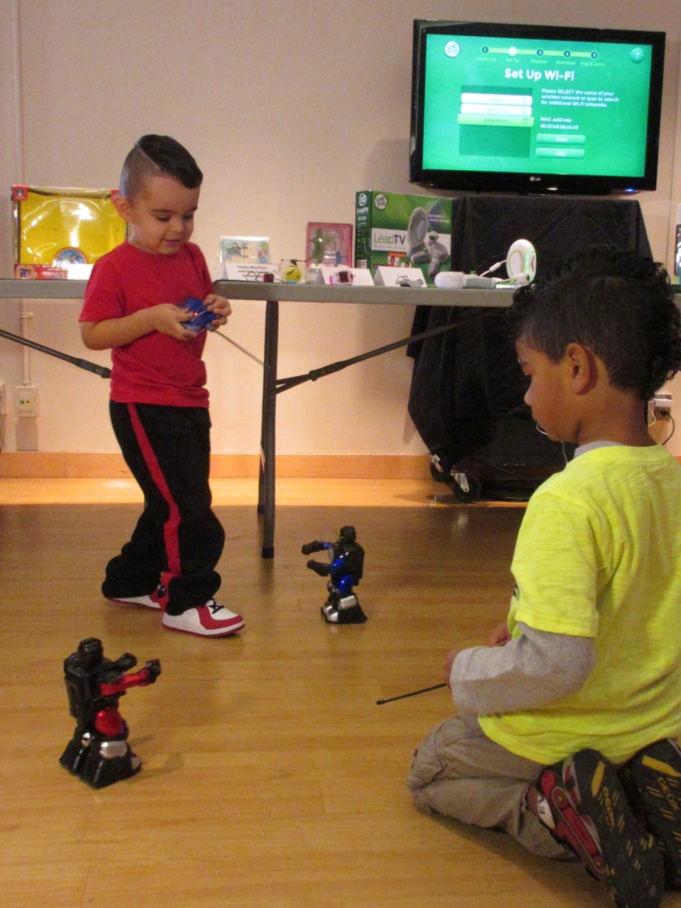 Two boys play with robots features in the 'Hot Toys for the Holidays' showcase in downtown Toronto on Tuesday, Nov. 4, 2014. (Angela Mulholland / CTVNews.ca)