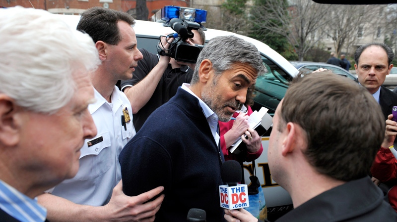 Actor George Clooney, centre, and Rep. Jim Moran, D-Va., left, are led to a police vehicle after being arrested during a protest at the Sudan Embassy in Washington, Friday, March 16, 2012. (AP / Cliff Owen)