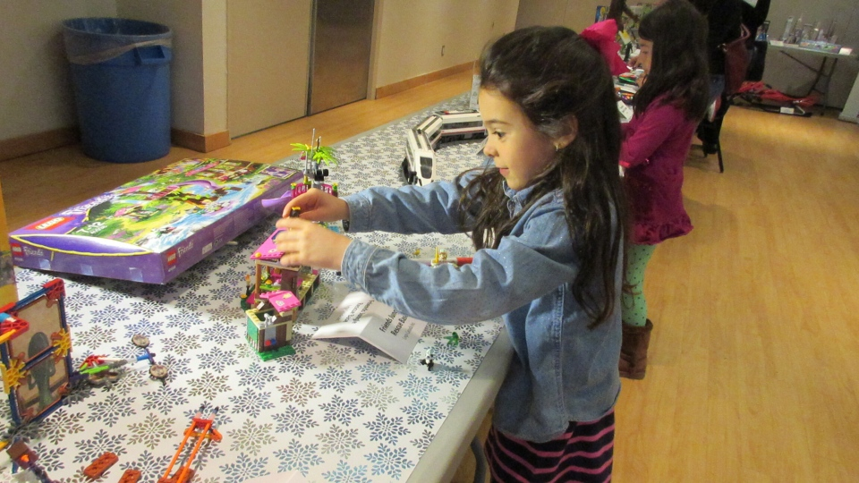 A young girl plays with LEGO at the 'Hot Toys for the Holidays' showcase in downtown Toronto on Tuesday, Nov. 4, 2014. (Angela Mulholland / CTVNews.ca)