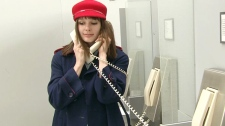 A passenger tries to rebook her flight using an Air Canada courtesy phone at Pearson International Airport on Sunday, March 18, 2012.
