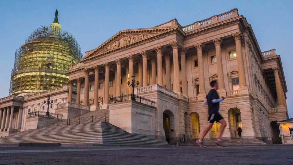 A jogger runs by the Senate side of the US Capitol in Washington at dawn on Nov. 4, 2014. (AP / J. David Ake)