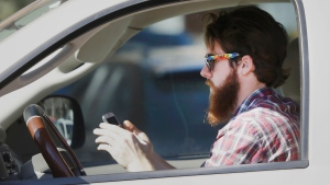 A man uses his cell phone as he drives through traffic in Dallas, on Feb. 26, 2013. (AP / LM Otero)