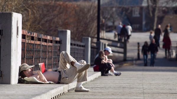 Steven Anderson reads a book and enjoys the sunshine on a bridge at Cedarvale Park in Toronto on Sunday, March 11, 2012.(Pawel Dwulit / THE CANADIAN PRESS)