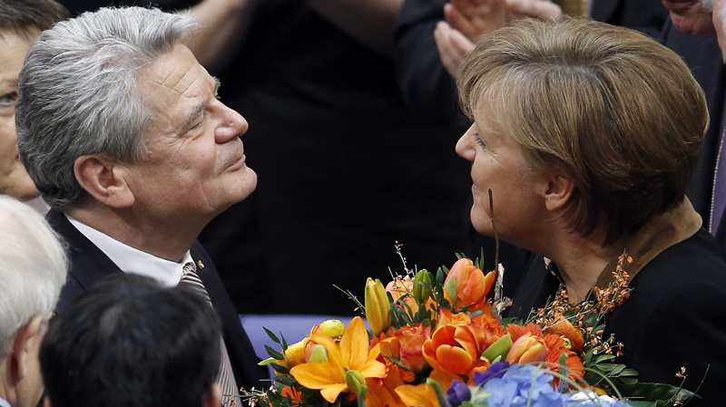 German Chancellor Angela Merkel, right, hands over a bunch of flowers to the new elected German President Joachim Gauck, left, at the parliament building Reichstag in Berlin, Germany, Sunday, March 18, 2012.  (AP Photo/Michael Sohn)