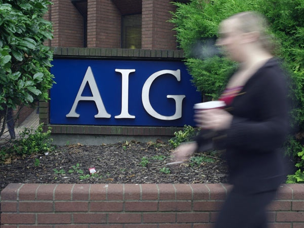 A woman walks past the office of U.S. insurance giant AIG, American International Group, in Croydon, South London, Tuesday, Sept. 16, 2008. (AP Photo / Sang Tan)