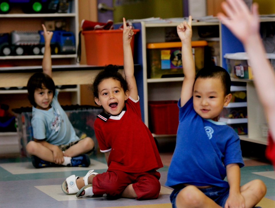 Children put up their hands at a daycare centre in Montreal on Friday, August 18, 2006. (Ian Barrett / THE CANADIAN PRESS)