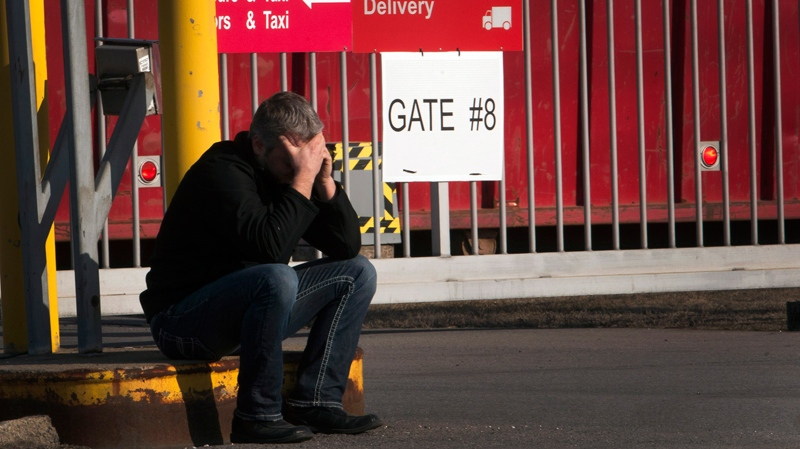 A laid off Aveo employee makes a call in front of the aircraft maintenance company's plant in Montreal, Tuesday, March 20, 2012. (Ryan Remiorz / THE CANADIAN PRESS)
