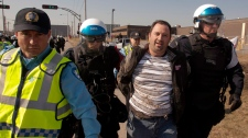A laid-off Aveo employee is arrested during a demonstration in front of the aircraft maintenance company's plant in Montreal, Tuesday, March 20, 2012. (Ryan Remiorz / THE CANADIAN PRESS)