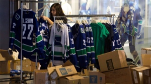 An employee at the Vancouver Canucks store unpacks merchandise at Rogers Arena. (Jonathan Hayward / THE CANADIAN PRESS)