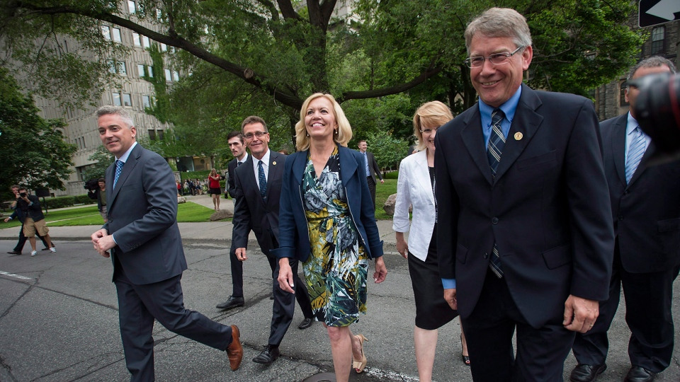 Christine Elliott, centre, widow of former federal Finance Minister Jim Flaherty, walks across University Avenue toward Queen's Park with supporters after announcing her intention to run for the Ontario PC leadership during a press conference in Toronto on Wednesday, June 25, 2014. (Darren Calabrese / THE CANADIAN PRESS)
