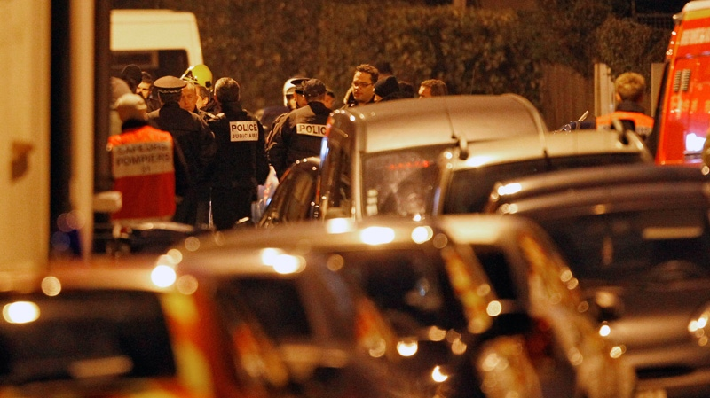 French police officers and firefighters stand at night next to the apartment building where a suspect in the shooting at the Ozar Hatorah Jewish school is still barricaded, in Toulouse, Southern France, Wednesday, March 21, 2012. (AP / Christophe Ena)