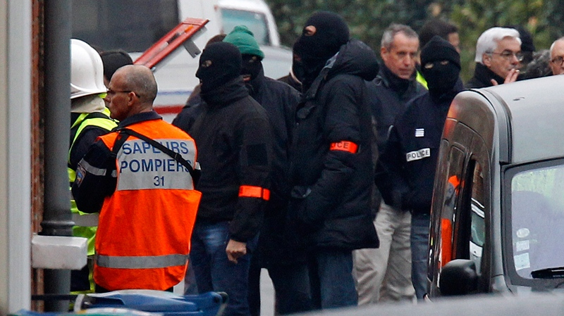 Police officers and firefighters stand near a building in Toulouse, France, Wednesday, March 21, 2012. (AP / Remy de la Mauviniere)