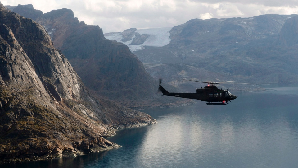 A Canadian military Griffon helicopter flies along the shoreline of Baffin Island as it moves personnel between Op Nanook and Iqaluit Tuesday August 26, 2014. (Adrian Wyld / THE CANADIAN PRESS)