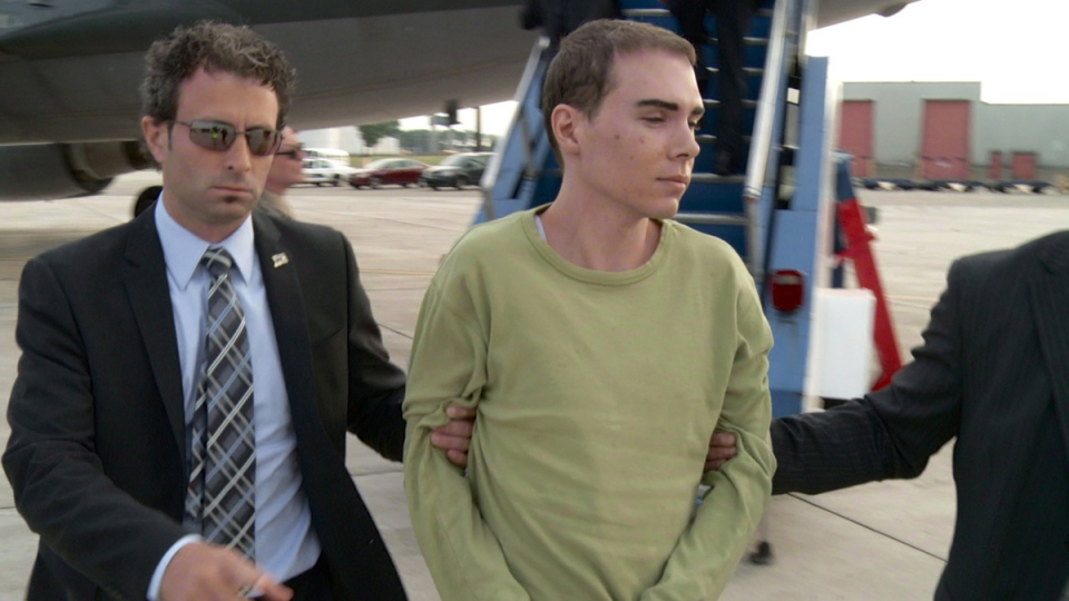Luka Rocco Magnotta is taken by police from a Canadian military plane to a waiting van on June 18, 2012 in Mirabel, Quebec. (THE CANADIAN PRESS)