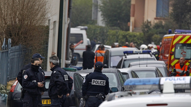 Police officers and firefighters stand next to a building in Toulouse, France, Wednesday, March 21, 2012 where a suspect in the shooting at the Ozar Hatorah Jewish school was believed baricaded. (AP Photo/Remy de la Mauviniere)