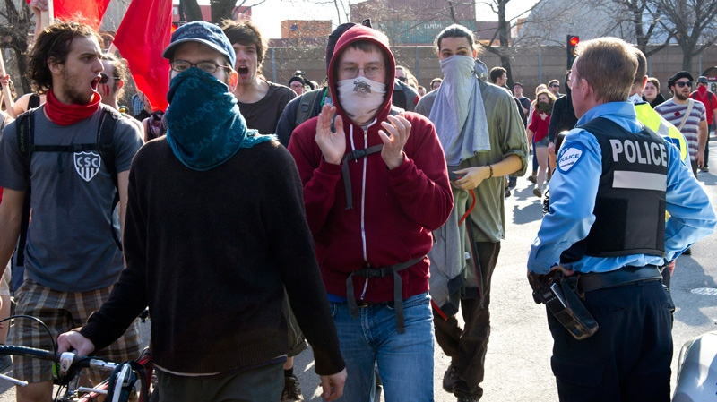 Protesting students march past a police officer as they try to block the Port of Montreal during a demonstration against tuition hikes Thursday, March 22, 2012 in Montreal.  (Paul Chiasson / THE CANADIAN PRESS)
