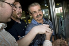 An unidentified man pushes away a Canadian Press reporter's microphone as he escorts Agriculture Minister Gerry Ritz out of the airport in Ottawa on Wednesday, Sept. 17, 2008. (Adrian Wyld / THE CANADIAN PRESS)