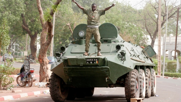 A soldier poses atop a military vehicle, as it stands guard outside the presidential palace following a military coup in Bamako, Mali, Friday, March 23, 2012. (AP / Harouna Traore)