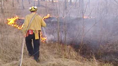 Crews battle a grass fire in the RM of Stuartburn in Manitoba on March 23, 2012 after bringing it under control on March 22.