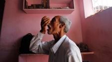 A tuberculosis patient takes medicines at Directly Observed Treatment Short-course, run by non-government organization Navirman Samaj Vikas Kendra, on the outskirts of Mumbai, India, Monday, Jan. 16, 2012.