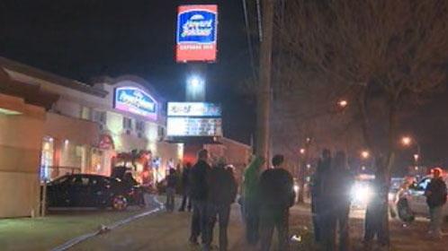 A crowd looks on as fire crews deal with a blaze at the Howard Johnson Inn.