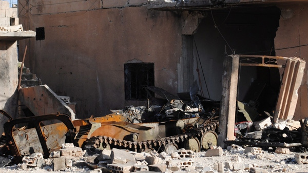 In this picture taken on Tuesday March 20, 2012, a damaged part of a Syrian army tank that attacked by the Syrian rebels is seen next to a destroyed house , at Rastan town in Homs province, central Syria. (AP)