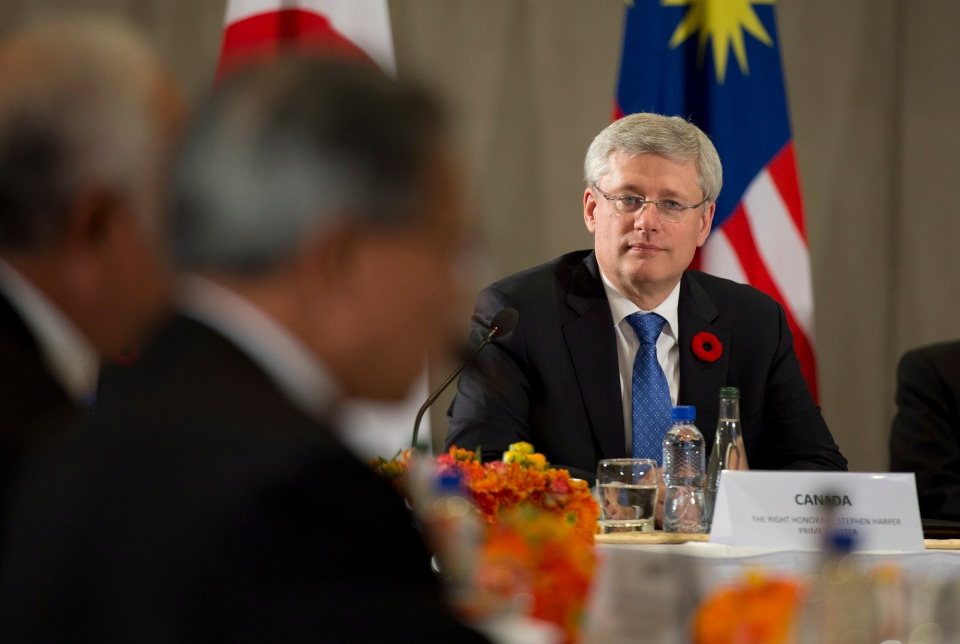 Canadian Prime Minister Stephen Harper listens to United States President Barack Obama deliver opening remarks to members of the Trans Pacific Partnership at the US Embassy in Beijing, China, on Monday, November 10, 2014. (THE CANADIAN PRESS/Adrian Wyld)