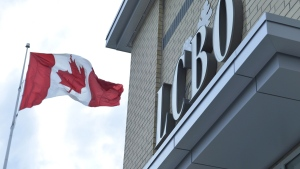 A Canadian flag flies near an under-construction LCBO store in Bowmanville, Ont. on Saturday, July 20, 2013. A union president is recommending consumers stock up to celebrate Canada Day in anticipation of a possible strike of LCBO workers Monday. (File / THE CANADIAN PRESS)