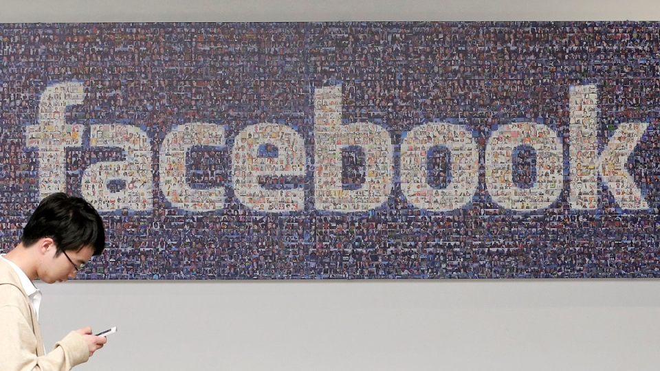 A man walks past a sign in an office on the Facebook campus in Menlo Park, Calif. on June 11, 2014.  (AP / Jeff Chiu)