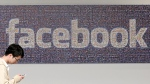 A man walks past a sign in an office on the Facebook campus in Menlo Park, Calif. on June 11, 2014. (Jeff Chiu/AP)