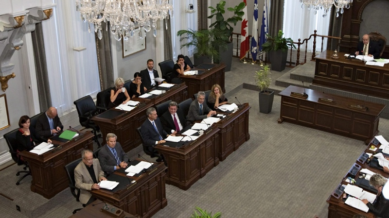 Quebec City Mayor Regis Labeaume, centre, front row fourth from the left, flanked by municipal counselors sit at the municipal council room Tuesday, September 6, 2011 in Quebec City for a briefing over the signed agreement with Pierre Karl Peladeau and Quebecor on the management of a future arena.