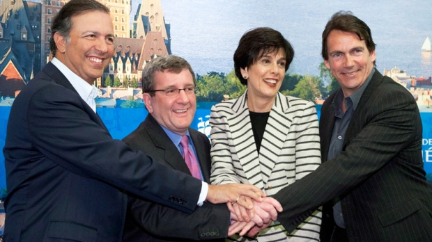 Quebecor president Pierre Karl Peladeau, from left, Quebec City Mayor Regis Labeaume, Quebec Treasury Board president Michelle Courchesne and Sam Hamad join hands after they announced they are going to proceed and build an arena Sunday, March 25, 2012 in Quebec City. (Jacques Boissinot / THE CANADIAN PRESS)