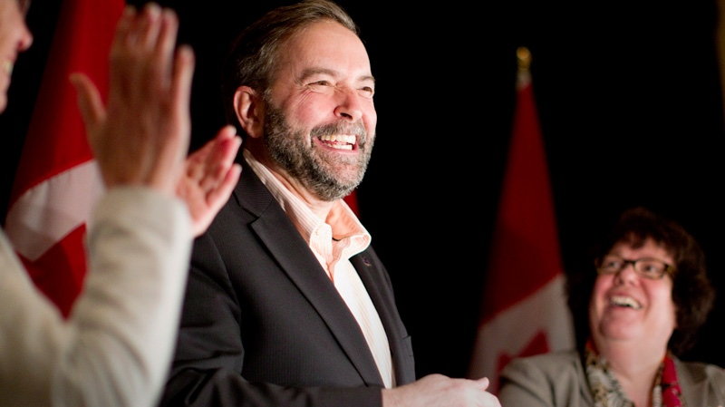 Newly-elected NDP Leader Thomas Mulcair (centre) is flanked by former interim leader Nycole Turmel and former deputy leader Libby Davies (right) as he receives applause at a party caucus meeting in Toronto on Sunday, March 25, 2012. (Chris Young / THE CANADIAN PRESS)