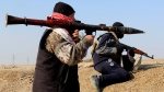 Islamic State group militants hold their weapons in their combat positions in Fallujah, 65 kilometres west of Baghdad, Iraq, Wednesday, Feb. 12, 2014. (AP)
